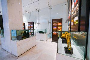 Khu tái hiện lịch sử hình thành mỏ than, bảo tàng Quảng Ninh, nhiều mô hình xe trong tủ kính trên bệ gạch màu trắng, bảng giới thiệu màu nâu, nền nhà bằng gạch màu trắng
