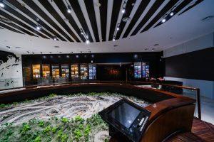 Khu tái hiện lịch sử hình thành mỏ than, bảo tàng Quảng Ninh, mô hình mỏ than có cây xanh, màn hình màu đen, trần nhà màu trắng có họa tiết đen