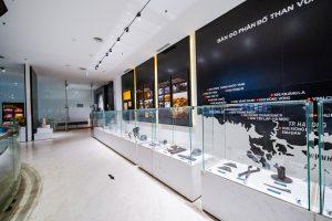 Khu tái hiện lịch sử hình thành mỏ than, bảo tàng Quảng Ninh, nhiều dụng cụ được bày trong tủ kính, bản đồ màu đen, nền gạch màu trắng có mũi tên màu đen nằm trên, trần nhà màu trắng