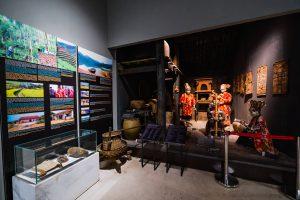 Khu tái hiện lịch sử hình thành mỏ than, bảo tàng Quảng Ninh, nhiều hiện vật được trưng bày trong tủ kính trên bệ đá màu trắng, bảng giới thiệu có hình ảnh màu đen, nhiều mô hình người mặc áo đỏ đội mũ, nền gạch có hoa văn