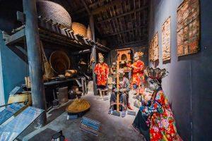 Khu tái hiện lịch sử hình thành mỏ than, bảo tàng Quảng Ninh, nhiều mô hình người đội mũ mặc áo đỏ, nền nhà màu nâu, nhiều dụng cụ nhà bếp bằng mây, tường nhà màu xám