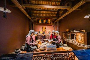 Khu tái hiện lịch sử hình thành mỏ than, bảo tàng Quảng Ninh, nhiều mô hình người đang ngồi ăn cơm, trần nhà bằng gỗ màu nâu, bức tường màu nâu