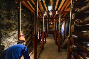 Khu tái hiện lịch sử hình thành mỏ than, bảo tàng Quảng Ninh, mô hình người công nhân mặc áo xanh, nhiều thanh gỗ to, nền đất màu nâu