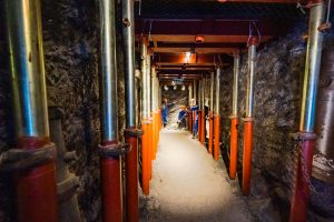 Khu tái hiện lịch sử hình thành mỏ than, bảo tàng Quảng Ninh, nền gạch bằng đá màu nâu, nhiều cột sắt sơn màu đỏ, mô hình người công nhân mặc quần áo xanh