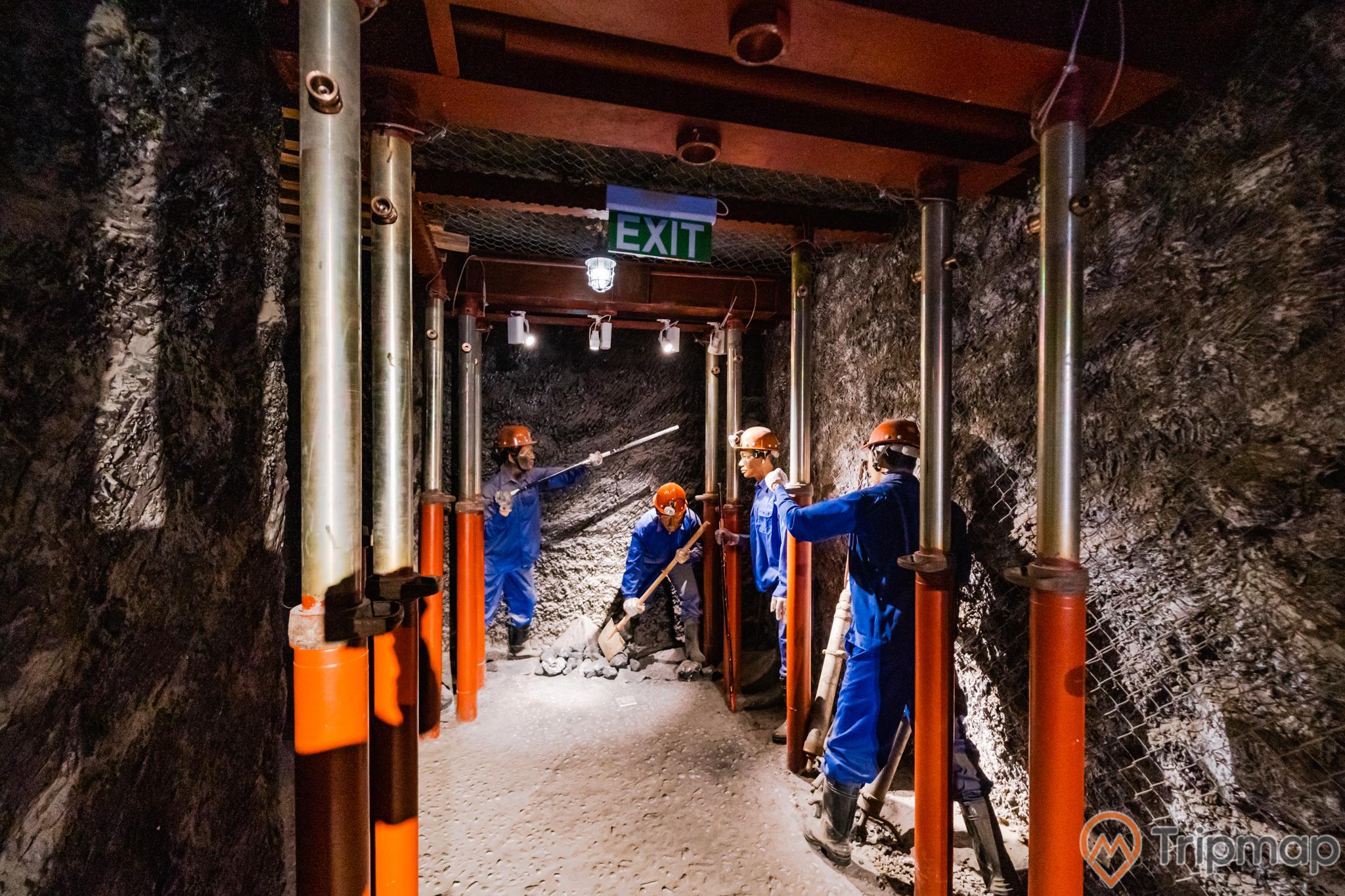 Khu tái hiện lịch sử hình thành mỏ than, bảo tàng Quảng Ninh, nhiều mô hình công nhân mặc quần áo xanh đang làm việc, nền đất màu xám, nhiều cây cột sắt sơn màu đỏ