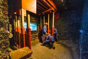 Khu tái hiện lịch sử hình thành mỏ than, bảo tàng Quảng Ninh, mô hình nhiều người công nhân mặc quần áo xanh đang làm việc, nền đất màu nâu, ánh sáng vàng, màn hình ti vi