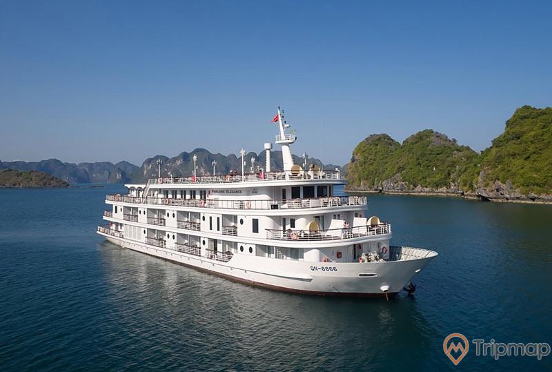 Tàu tham quan vịnh hạ long, ảnh chụp ban ngày, biển xanh, trời không mây, núi đá phía sau tàu, thàu thủy màu trắng 3 tầng đang đi trên biển