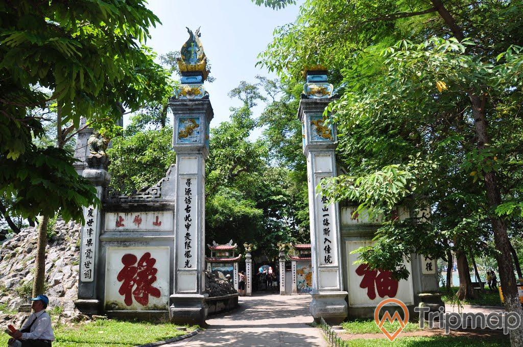 Cánh cổng khắc chữ trên tường và cây cối xanh tươi