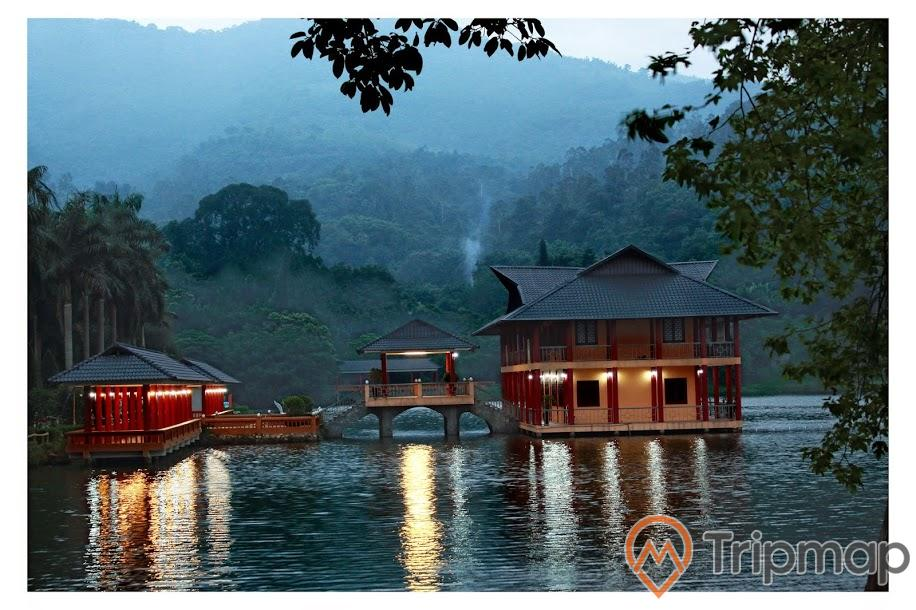 Nhà trên hồ khu du lịch Ao Vua, ngôi nhà bật đèn lun linh trên mặt hồ, cây cối ven hồ và trên đồi núi phía xa, ảnh chụp xế chiều