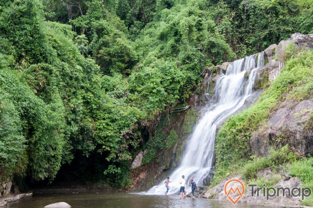 thác nước khu du lịch Ao vua, thác nước đang chảy xuống hồ nước, cây cối mọc trên vách núi, mọi người đang đứng dưới thác nước,
