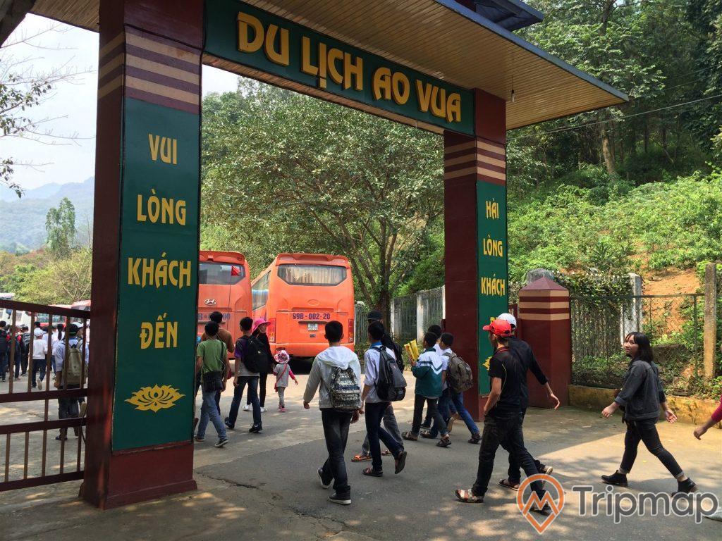 Cổng chào khu du lịch Ao Vua, mọi người đang đi vào bên trong cổng, oto khách, cây cối mọc ven đồi, bầu trời có nắng