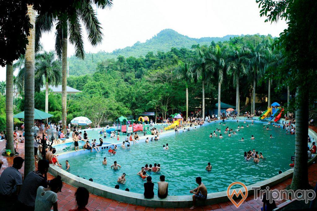 bể bơi ngoài trời khu du lịch Ao Vua, mọi người đang tắm trong bể bơi, cây cối ở ven bể bơi và trên dồi núi đồi phía xa