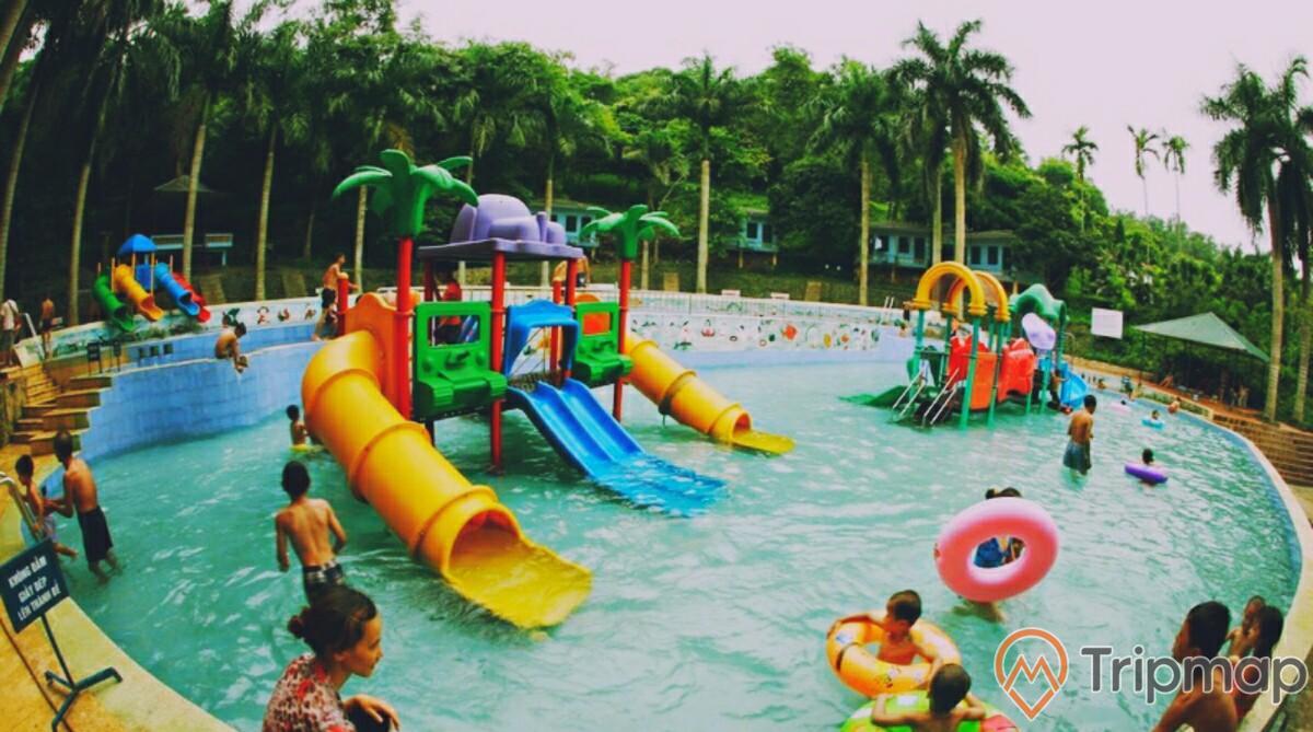 bể bơi trẻ em khu du lịch Ao Vua, mọi người đang tắm trong bể bơi, cầu trượt ở giữa bể bơi, cây cối xung quanh bể bơi, bầu trời nhiều mây
