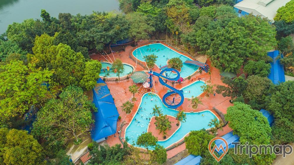 Khu bể bơi tại khu du lịch Ao Vua, bể bơi nước màu xanh, cầu trượu uốn lượn và cây cối xanh tươi xung quanh khu bể bơi, ảnh chụp bể bơi từ trên cao