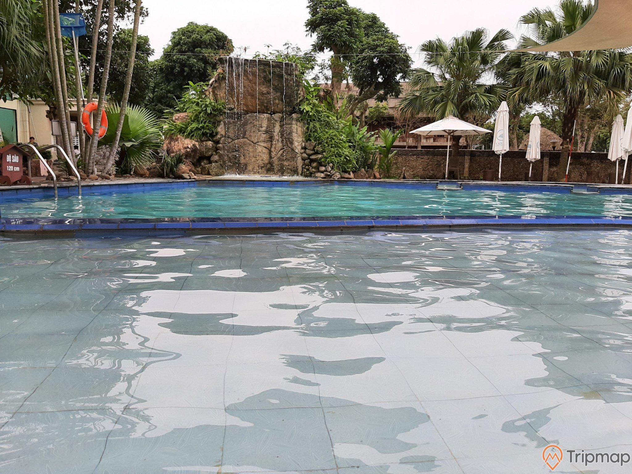 cái ô màu trắng cạnh bể bơi nước khoáng, thác nước nhận tạo cạnh bể bơi, 2 cây cọ và cây cối gần bể nước