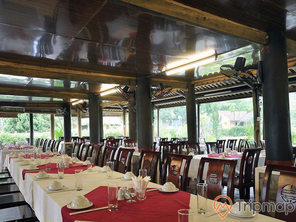 nhà hàng, bàn ăn và ghế xếp ngay ngắn trong nhà hàng, cốc nước và bát đĩa ở trên bàn màu đỏ trắng, có chiếc quạt treo trên cái cột