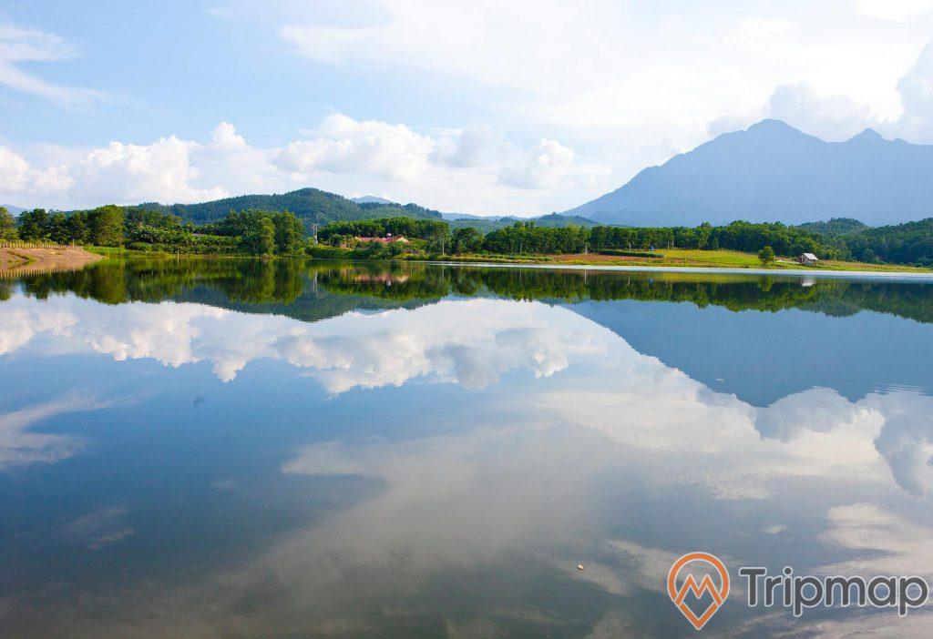 ảnh chụp núi đồi và bầu trời trong xanh nhiều mây phản chiếu xuống hồ nước,
