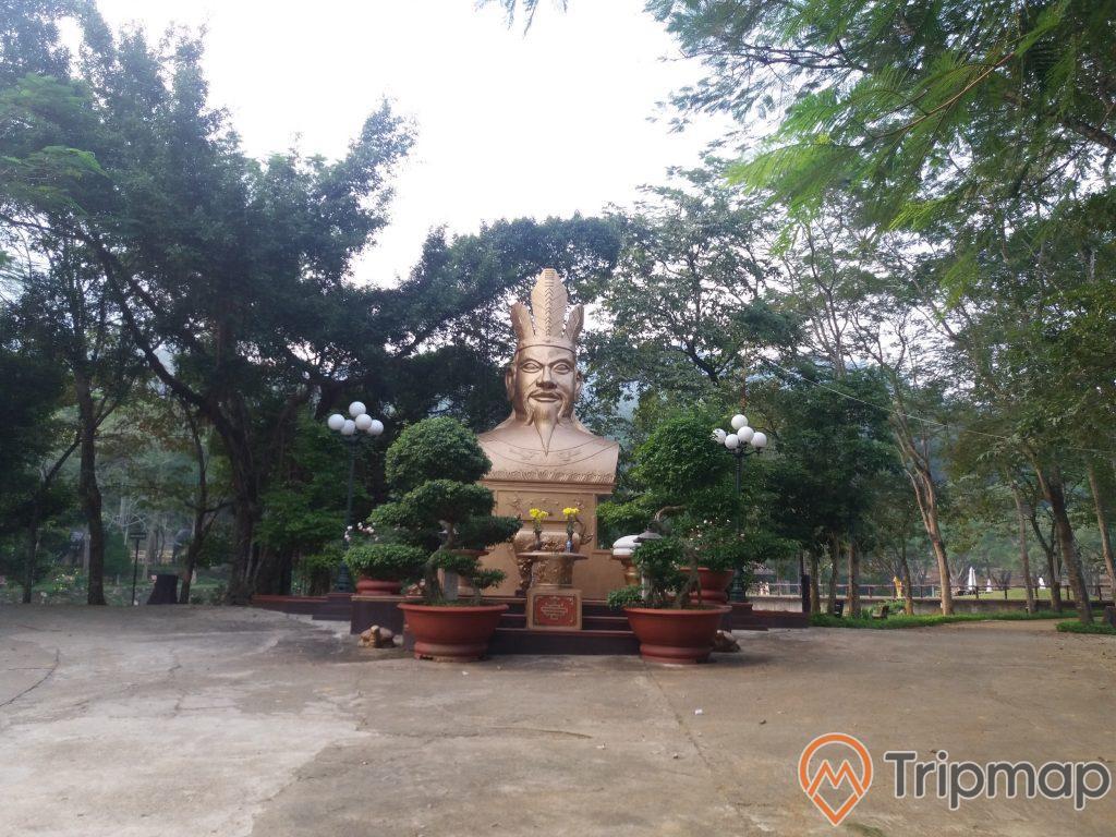 khuôn viên thờ cúng vua Hùng Vương tai khu du lịch Thác Đa, chậu cây cảnh trước tượng thờ, cây cối phía sau bức tượng, ảnh chụp ngoài trời