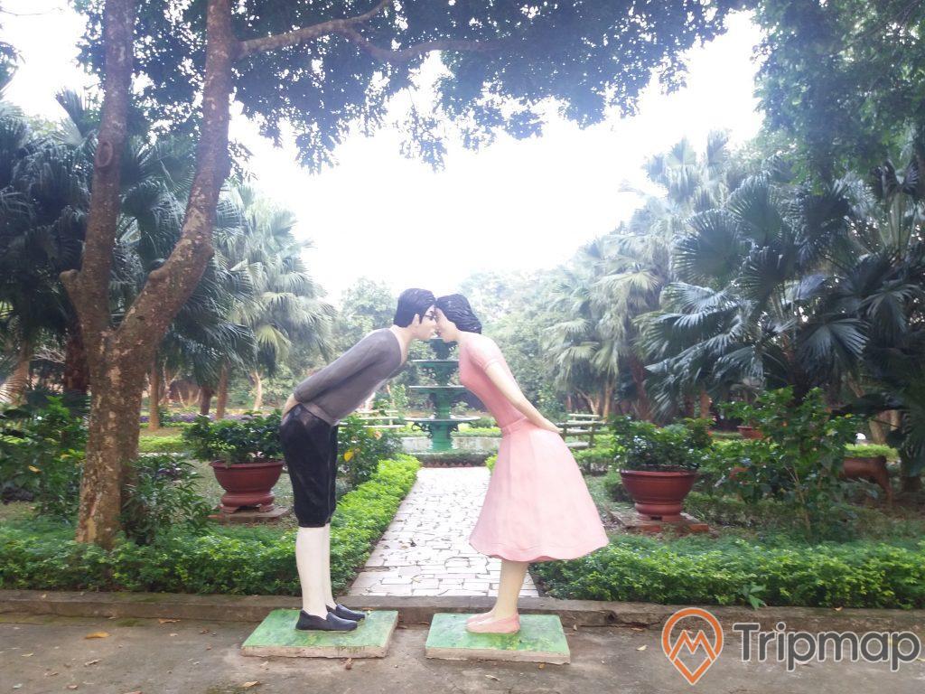 khu vườn tình yêu trong khu du lịch Thác Đa, 2 bức tượng nam nữ đang hôn nhau, 2 chậu cây cảnh và cây cối trong vườn