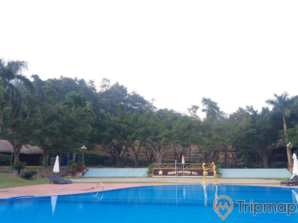 Bể bơi trong khu du lịch Thác Đa, bể bơi màu xanh, có 2 bức tượng màu vàng, chậu cây cạnh bậc thềm cây cối mọc quanh bể bơi, bầu trời nhiều mây,