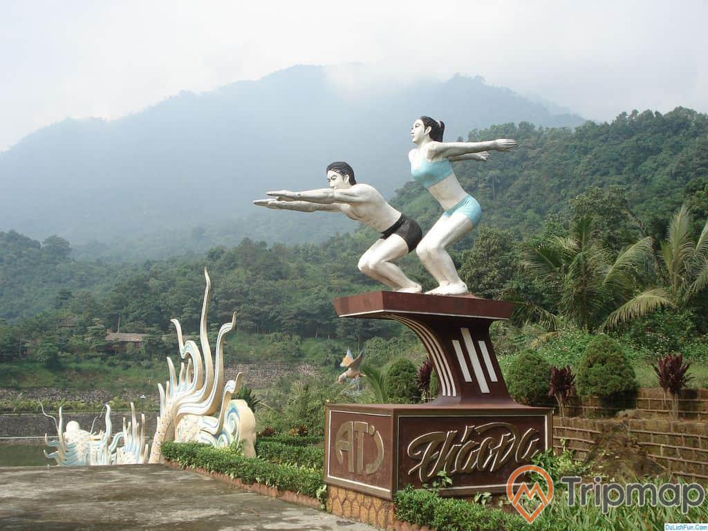 2 bức tượng đặt trên bệ xi măng màu nâu tại khu du lịch Thác Đa, phía xa cây cối xanh mọc phủ kín đồi núi, bầu trời có mây, ảnh chụp ngoài trời