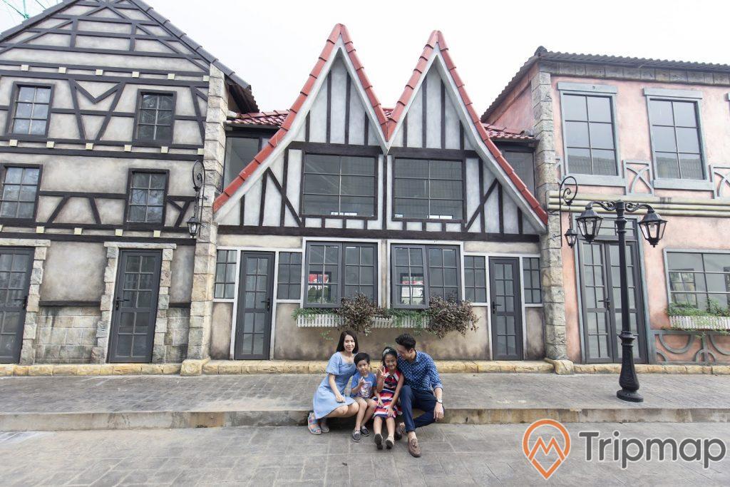 ngôi làng hoa Beuvron trong Thiên Đường Bảo Sơn, gia đình đang ngồi trước nhà tạo dáng chụp ảnh, 1 cây đèn trên vỉa hè, ảnh chụp ngoài trời