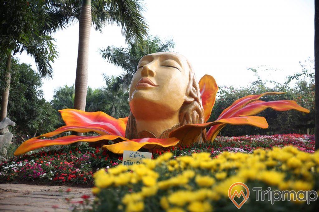 Thung lũng hoa trong Thiên Đường Bảo Sơn, bức tượng hình cô gái bên vườn hoa nhiều màu sắc, cây cối xanh mọc cao, bầu trời nhiều mây