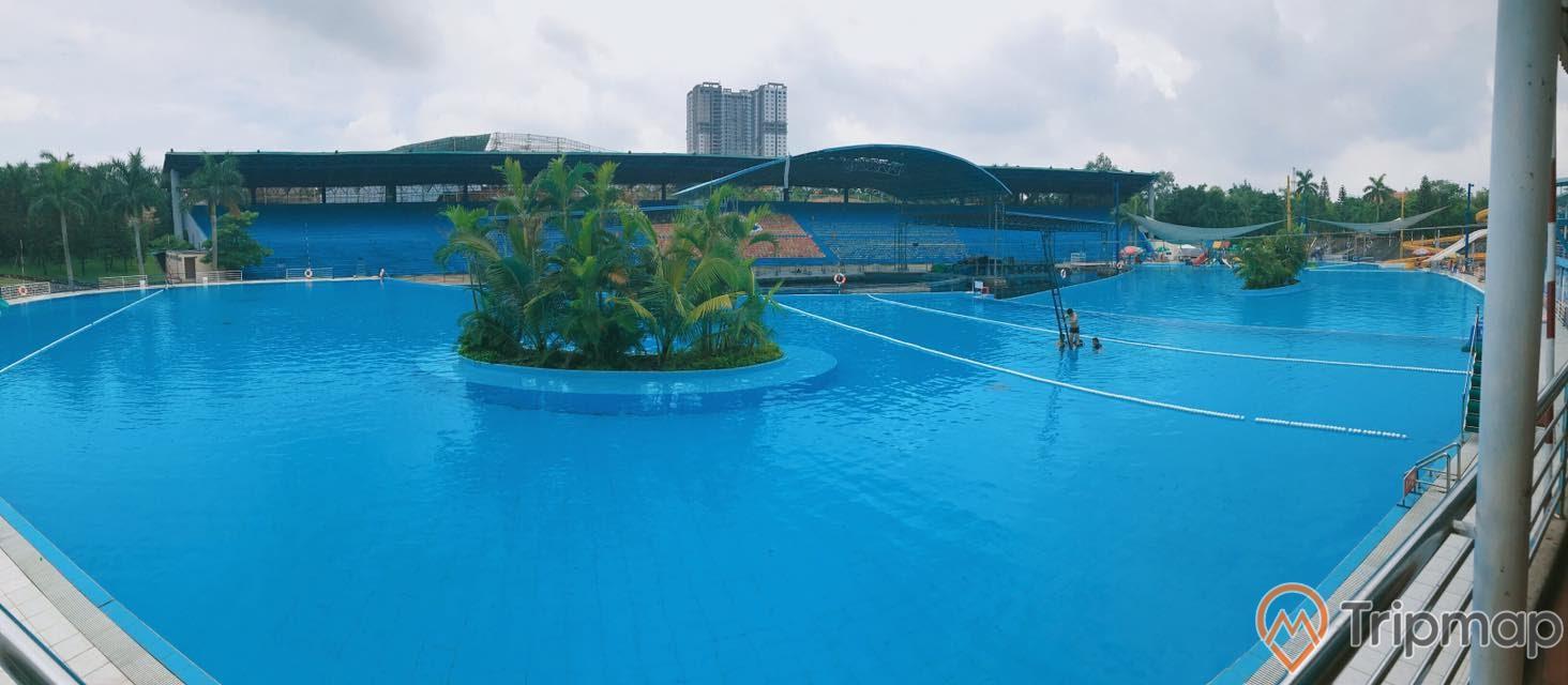 Bể bơi ngoài trời tại Thiên Đường Bảo Sơn, khóm cây xanh giữa bể bơi, khán đài ở phía bên kia bể nước, bầu trời nhiều mây, ảnh chụp ngoài trời