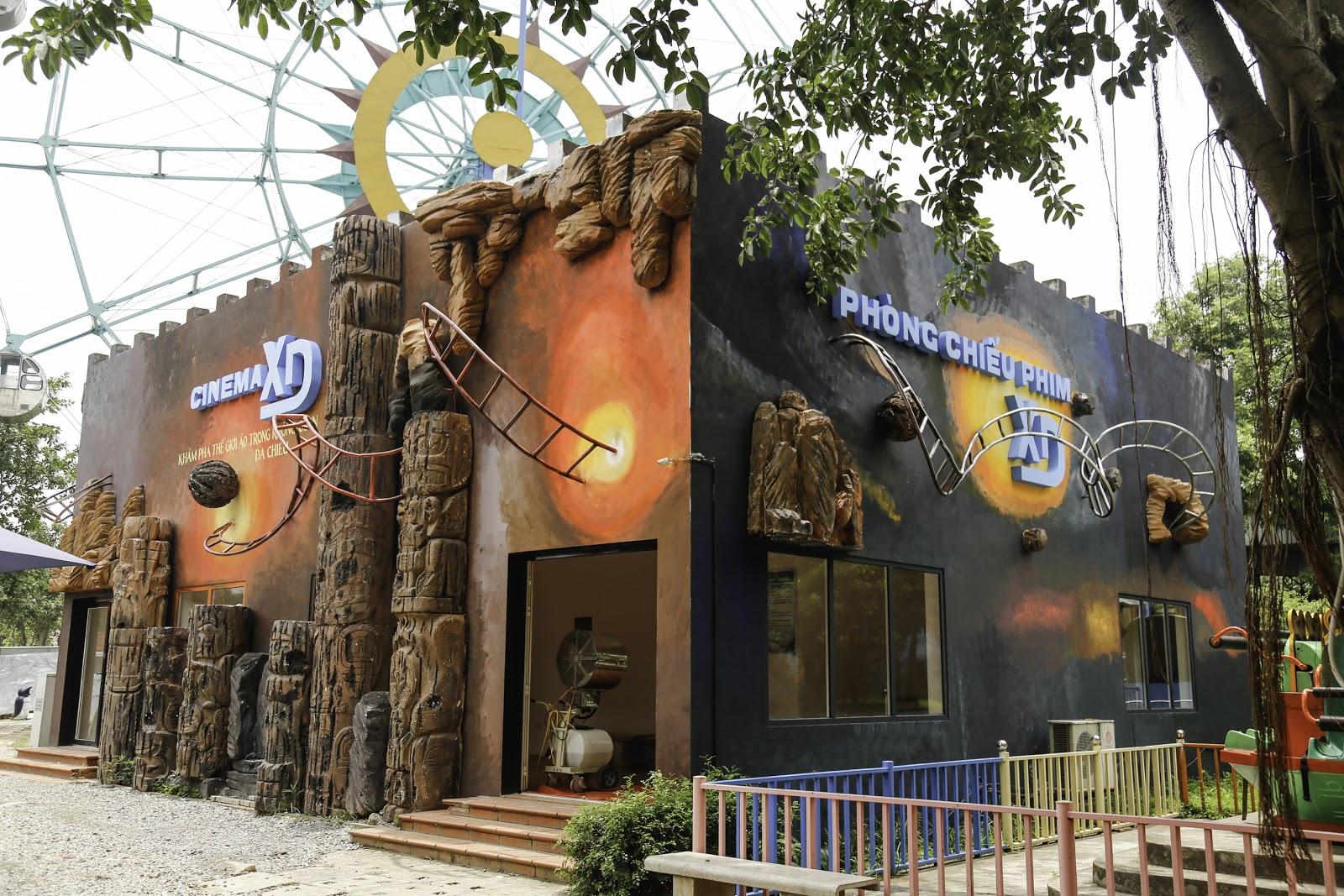 rạp chiếu phim XD tại Thiên đường Bảo Sơn, bên ngoài rạp chiếu phim trang trí nhiều màu sắc, trò chơi đu quay mặt trời phía sau cinema XD, ảnh chụp cạnh cái cây gần rạp chiếu chiếu XD,
