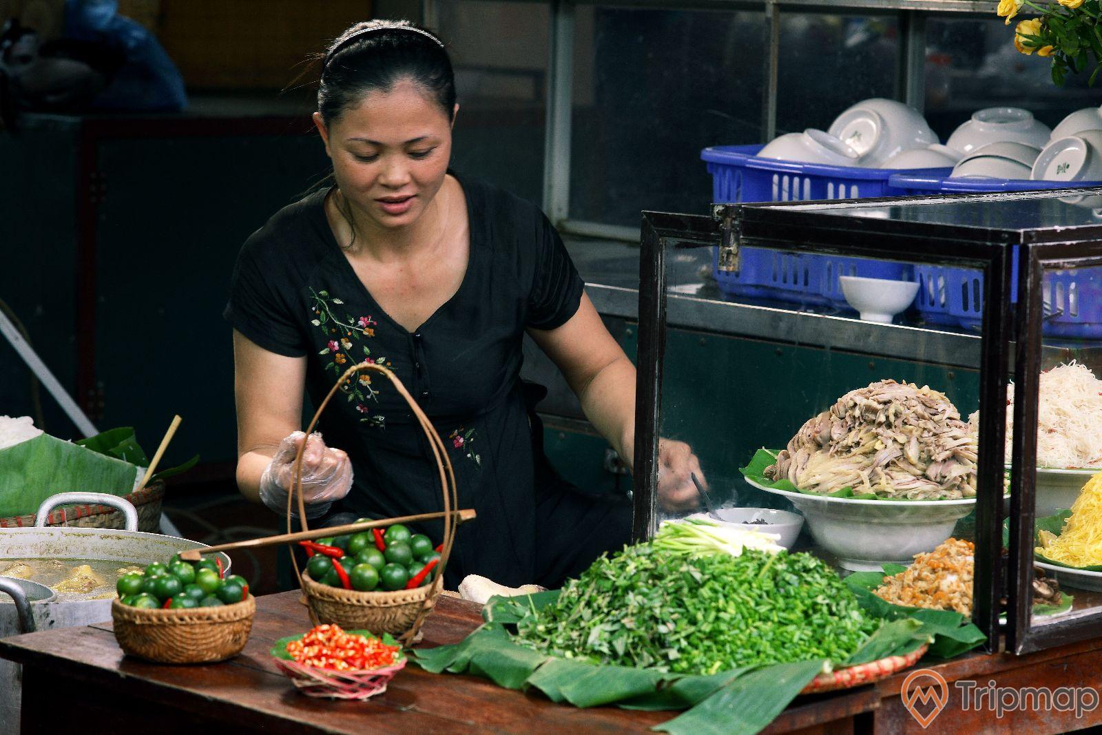 quán ăn khu ẩm thực tại Thiên đường Bảo Sơn, một người phụ nữ áo đen đang ngồi, đĩa mẹt hành gia vị hành và 1 giỏ ớt 2 giỏ quất trên bàn màu nâu, món ăn trong tủ kính, rổ bát màu xanh trên bàn, ảnh chụp phía trước của quán