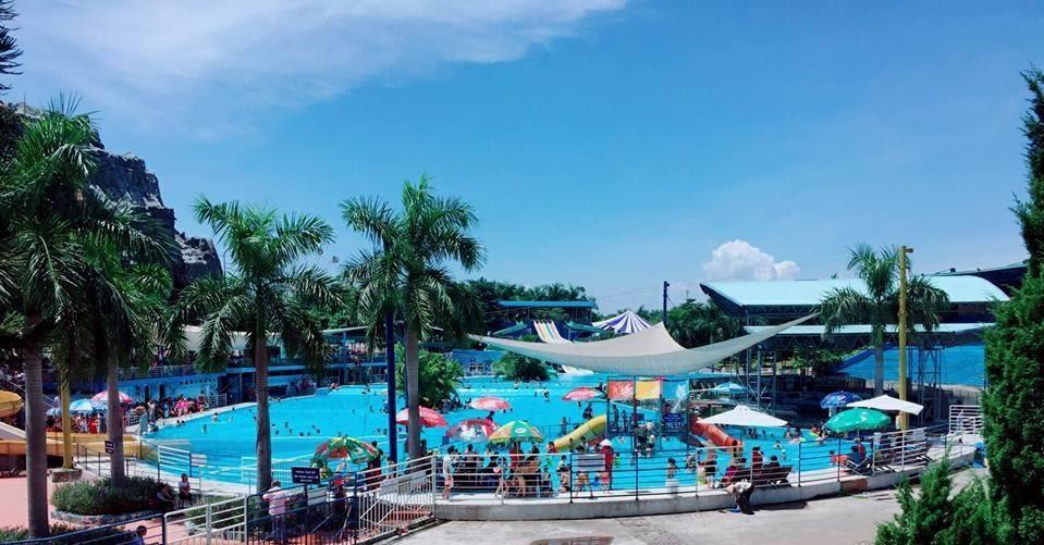 Công viên nước tại Thiên đường Bảo Sơn, mọi người đang tắm trong bể, cây cối mọc cạnh bể bơi, bầu trời xanh ít mây