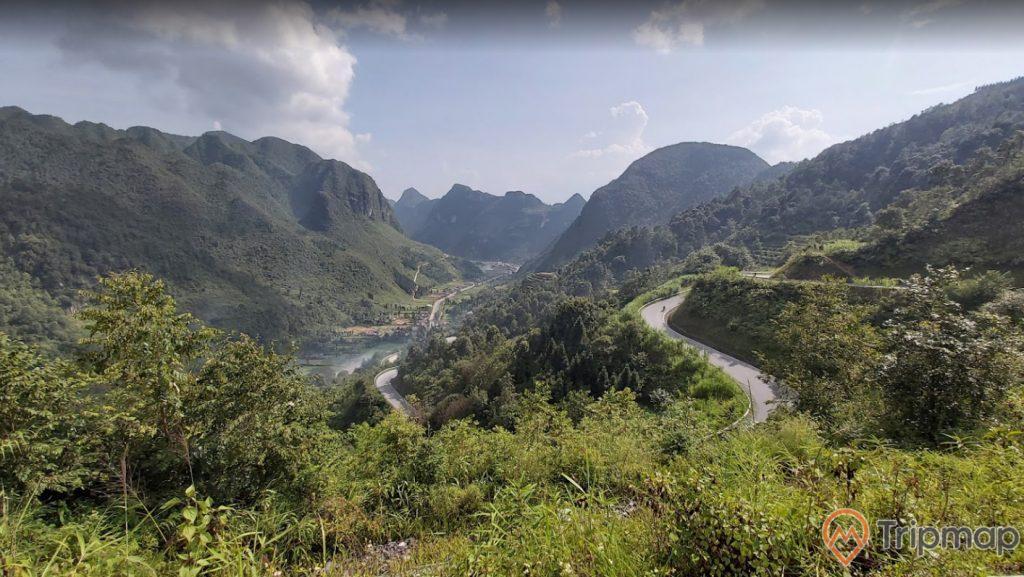 Dãy đồi núi tại cao nguyên Đồng Văn, đồi núi phía xa xa, đường đèo quanh co, cây cối xanh tươi trên đồi núi phía xa, bầu trời nhiều mây, ảnh chụp từ trên cao