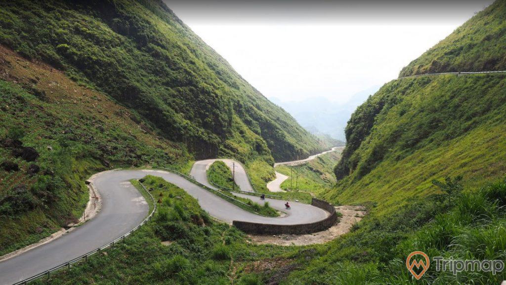 Dốc thẩm mã tại cao nguyên Đồng Văn, đường đèo quanh co, cây cỏ xanh tươi, bầu trời có mây, ảnh chụp ngoài trời