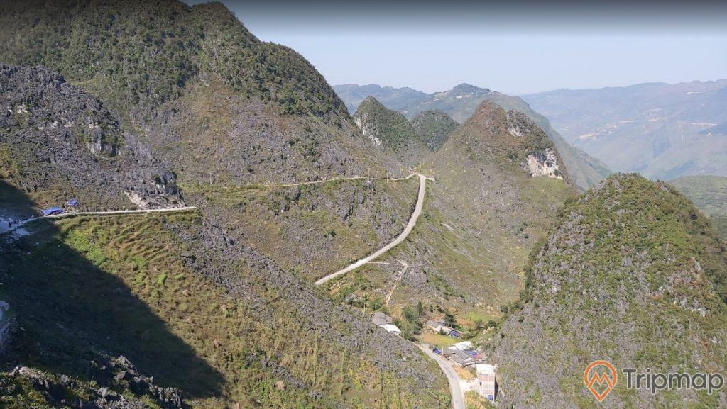 Quang cảnh đồi núi tại cao nguyên Đồng Văn, đường đèo trên sườn núi, cây cỏ xanh tươi trên đồi núi đá, ảnh chụp trên cao, bầu trời trong xanh