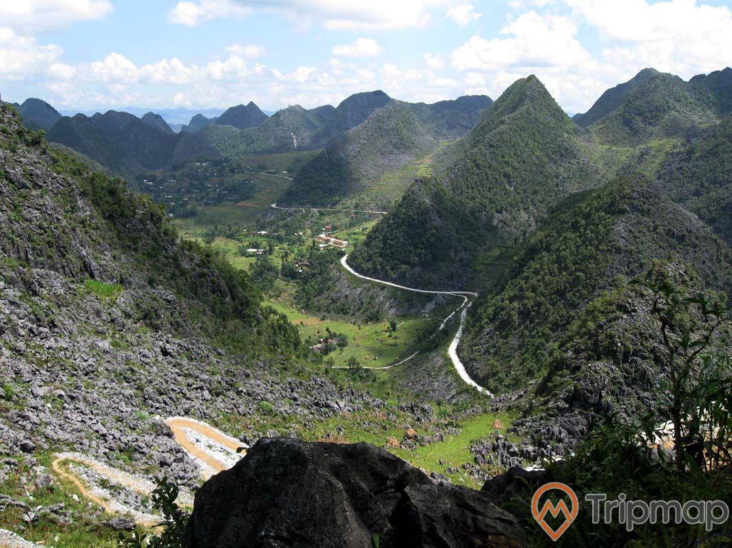 Quang cảnh thiên nhiên cao nguyên Đồng Văn, đường đèo bên sườn núi, đồi núi đá xanh tươi, bầu trời nhiều mây, ảnh chụp từ trên cao