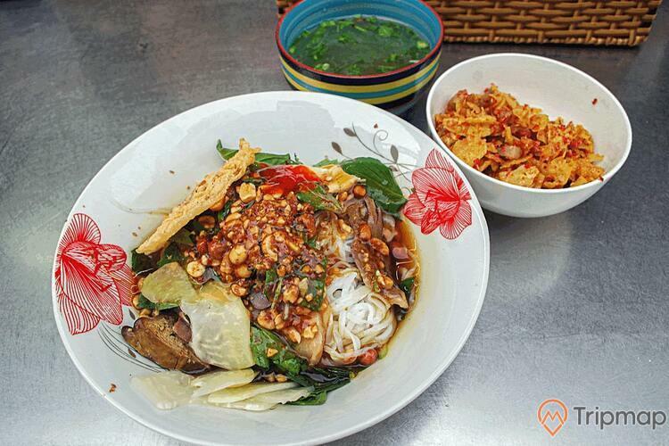 Món ăn đặc sản phở chua chợ tình khâu vai, bát phở chua với bát nước dùng và bát gia vị trên bàn inox
