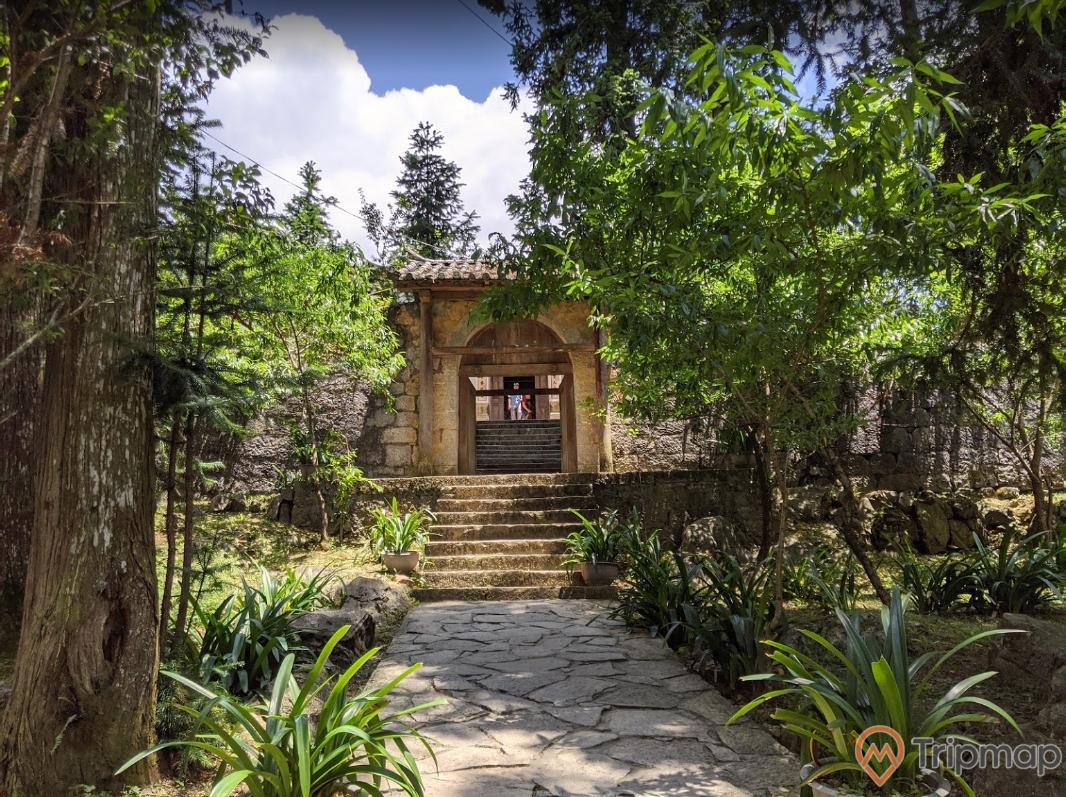 Lối đi vào bên trong khu dinh thự họ Vương, bậc thang đi vào cổng, cây cối xanh tươi phía ngoài sinh thự, bầu trời có mây, ảnh chụp ngoài trời