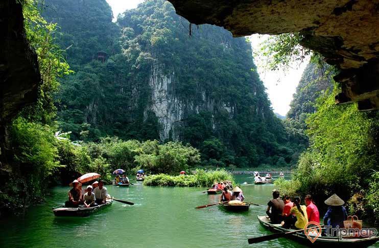 Quang cảnh trước hang động Phúc Long, mọi người ngồi trên thuyền đi trên dòng sông nước, núi đồi cây cối xanh tươi, ảnh chụp trong hang gần cửa động