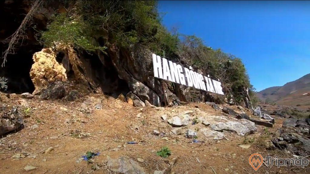 Khung cảnh gần hang động Xá Nhè, bầu trời trong xanh, cây cối xanh tươi trên vách đá gần hang động, ảnh chụp ngoài trời