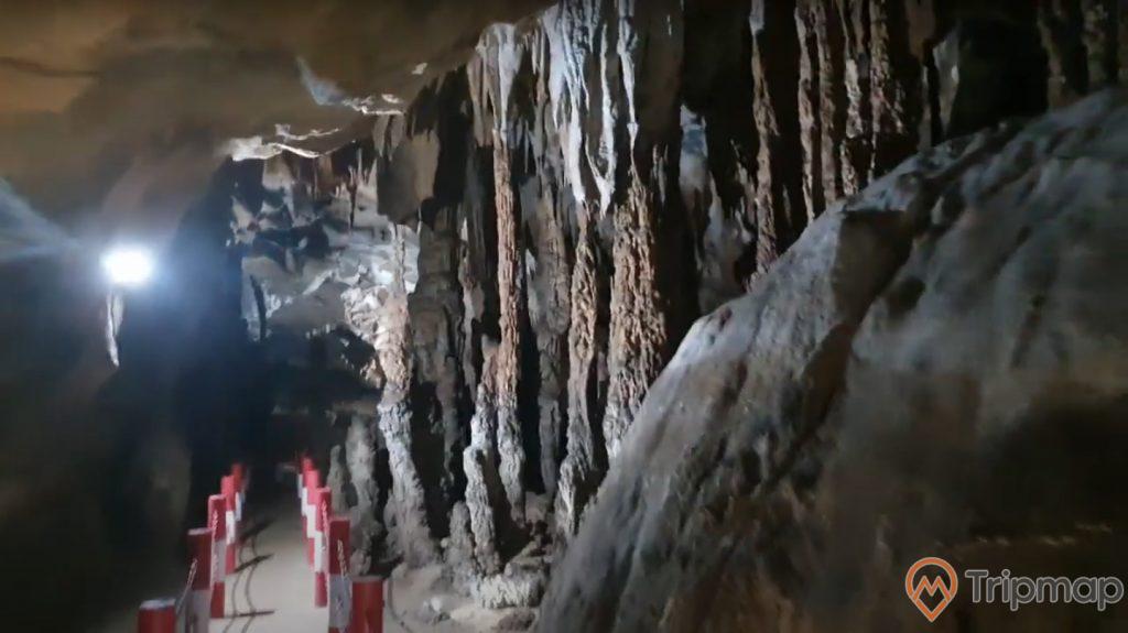 Cột nhũ đá trong hang động Xá Nhè, ánh đèn trắng trên vách đá, đường đi tham quan trong động, ảnh chụp trong hang động