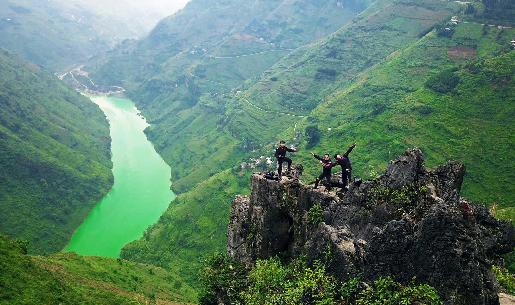 Quang cảnh thiên thiên cao nguyên Đồng Văn gần hang Phương Thiện, đồi núi xanh tươi, 3 người đứng tạo dáng trên ngọn núi đá, ảnh chụp từ trên cao