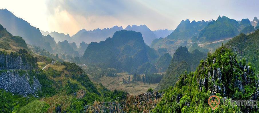 Qang cảnh thiên nhiên tuyệt đẹp gần hang Phương Thiện, bầu trời nhiều mây có nắng, đồi núi phía xa, cỏ cây xanh tươi trên các đồi núi cao, ảnh chụp từ trên cao