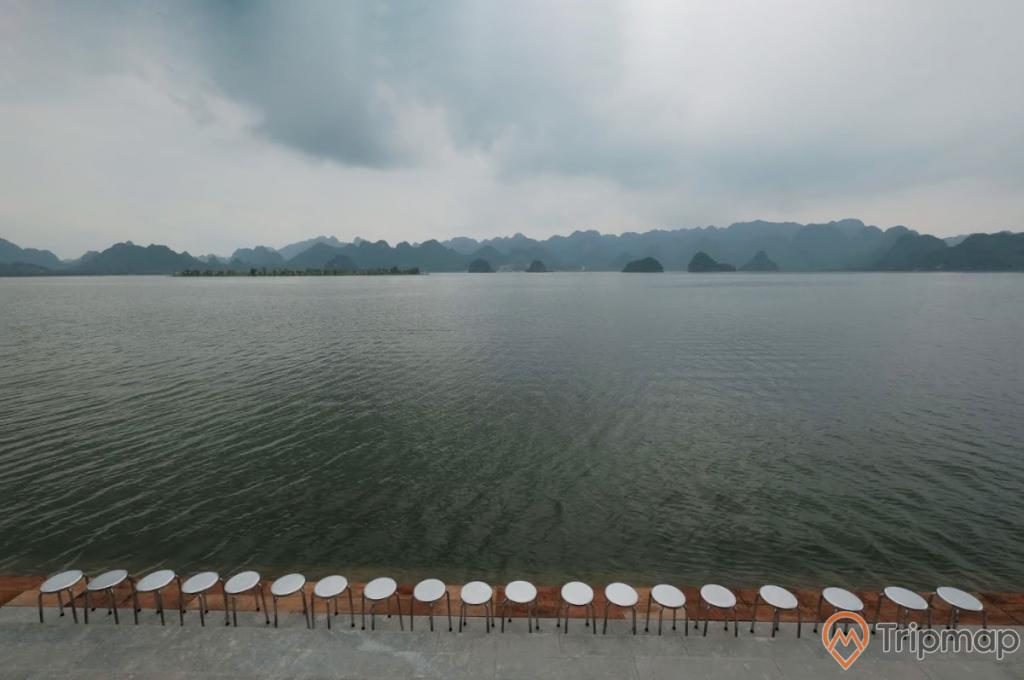Quang cảnh yên bình tại khu du lịch hồ Tam Chúc, hàng ghế inox trên bậc thềm bờ hồ, dãy núi đồi phía xa xa, bầu trời nhiều mây đen, ảnh chụp ngoài trời