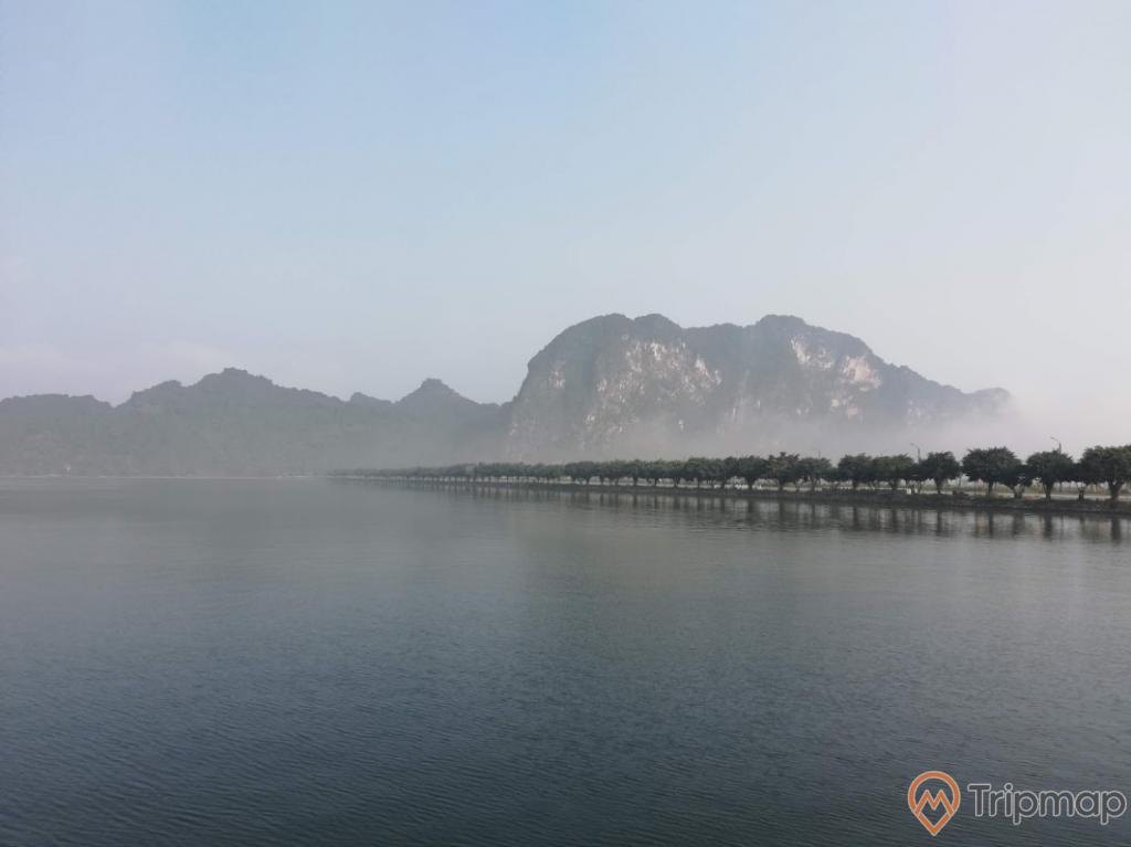 Khung cảnh chân trời tại khu du lịch hồ Tam Chúc, hàng cây hồ nước tam chúc, đồi núi phía xa xa, bầu trời nhiều mây, ảnh chụp ngoài trời