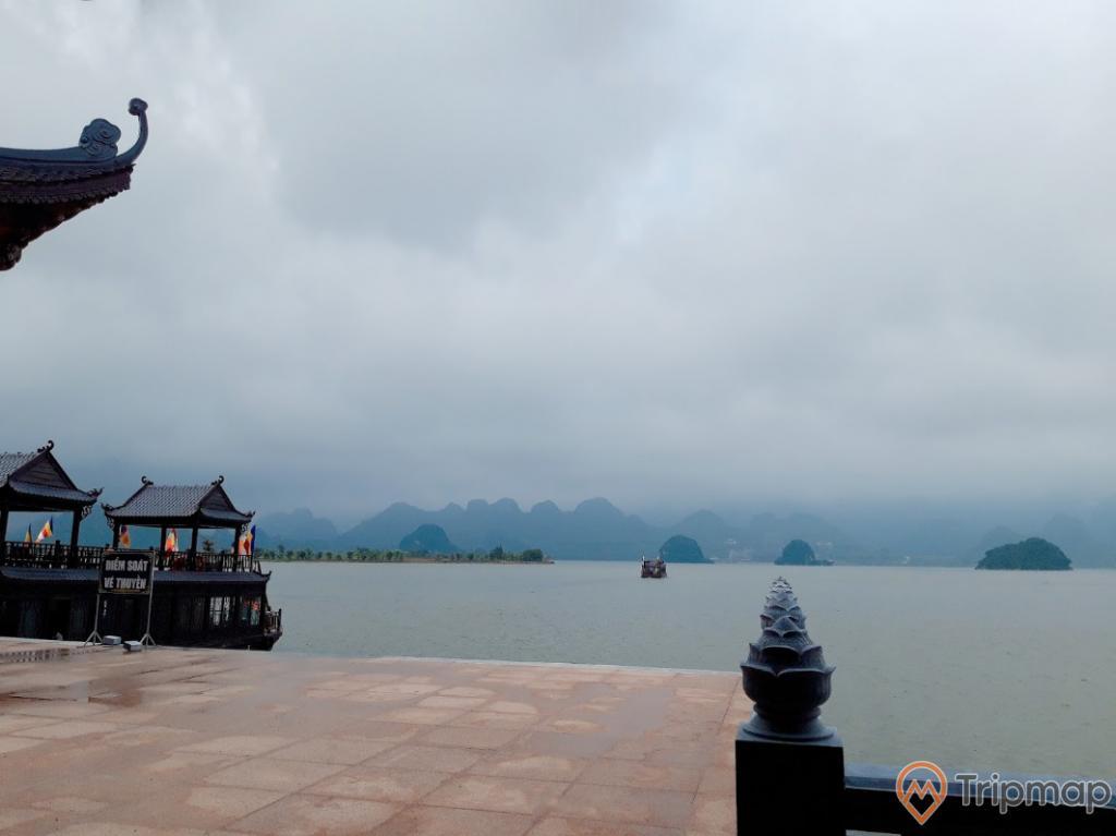 Bến đỗ du thuyền đón du khách tại khu du lịch hồ Tam Chúc, đồi núi phía xa xa, ảnh chụp ngoài trời, bầu trời nhiều mây đen