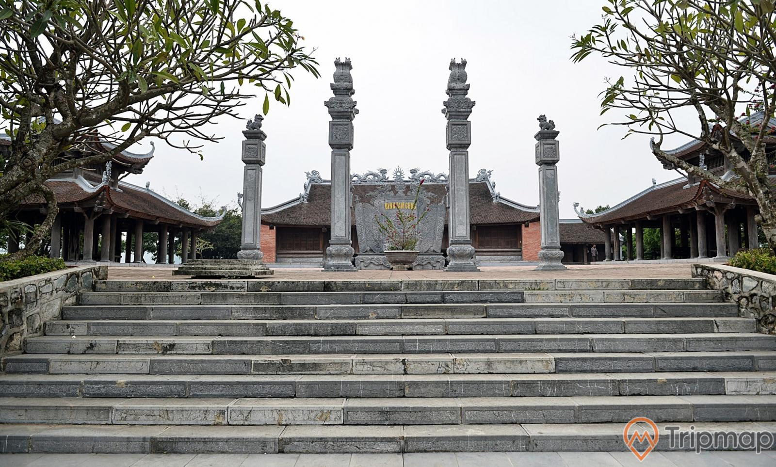 Đình Tam Chúc tại khu du lịch hồ tam chúc, bức bình phong bằng đá và tứ trụ bằng đá giữa sân đình, 2 bên bậc thềm bằng đá có 2 cây sứ, bầu trời nhiều mây, ảnh chụp ngoài trời