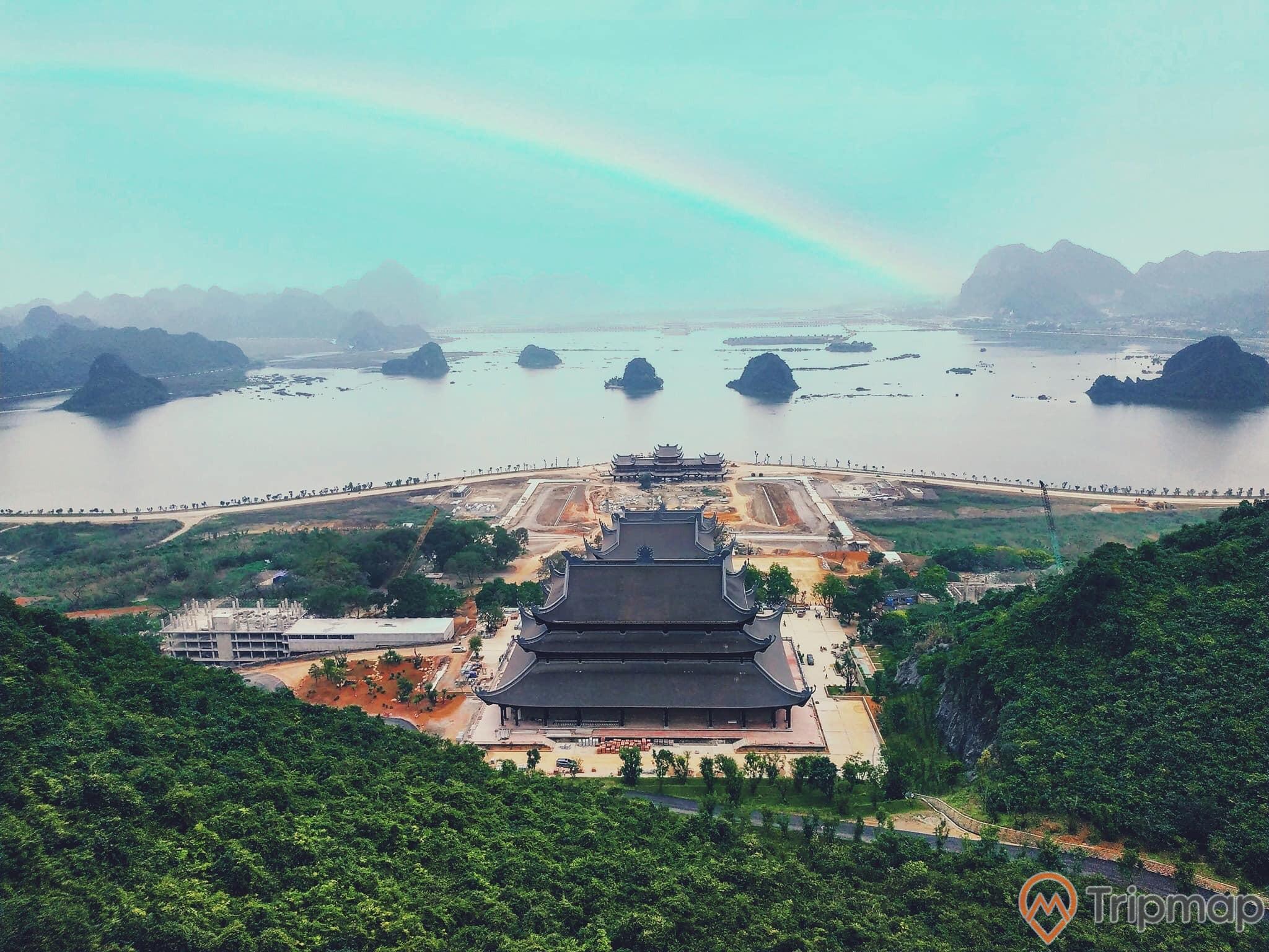 Quang cảnh thiên nhiên tại khu du lịch hồ tam chúc, đồi núi phía xa xa, bầu trời có mây, cây cối xanh tươi, ngôi chùa lớn nhất Đông Nam Á