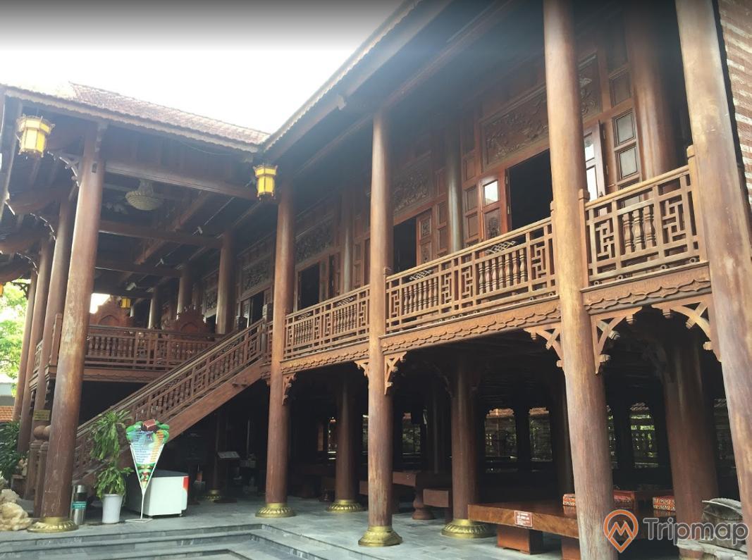 Nhà sàn gỗ Lim lớn nhất Việt Nam tại khu du lịch sinh thái Him Lam, ngôi nhà gỗ Lim 2 tầng, chậu cây cảnh ở chân cột, ảnh chụp ngoài trời