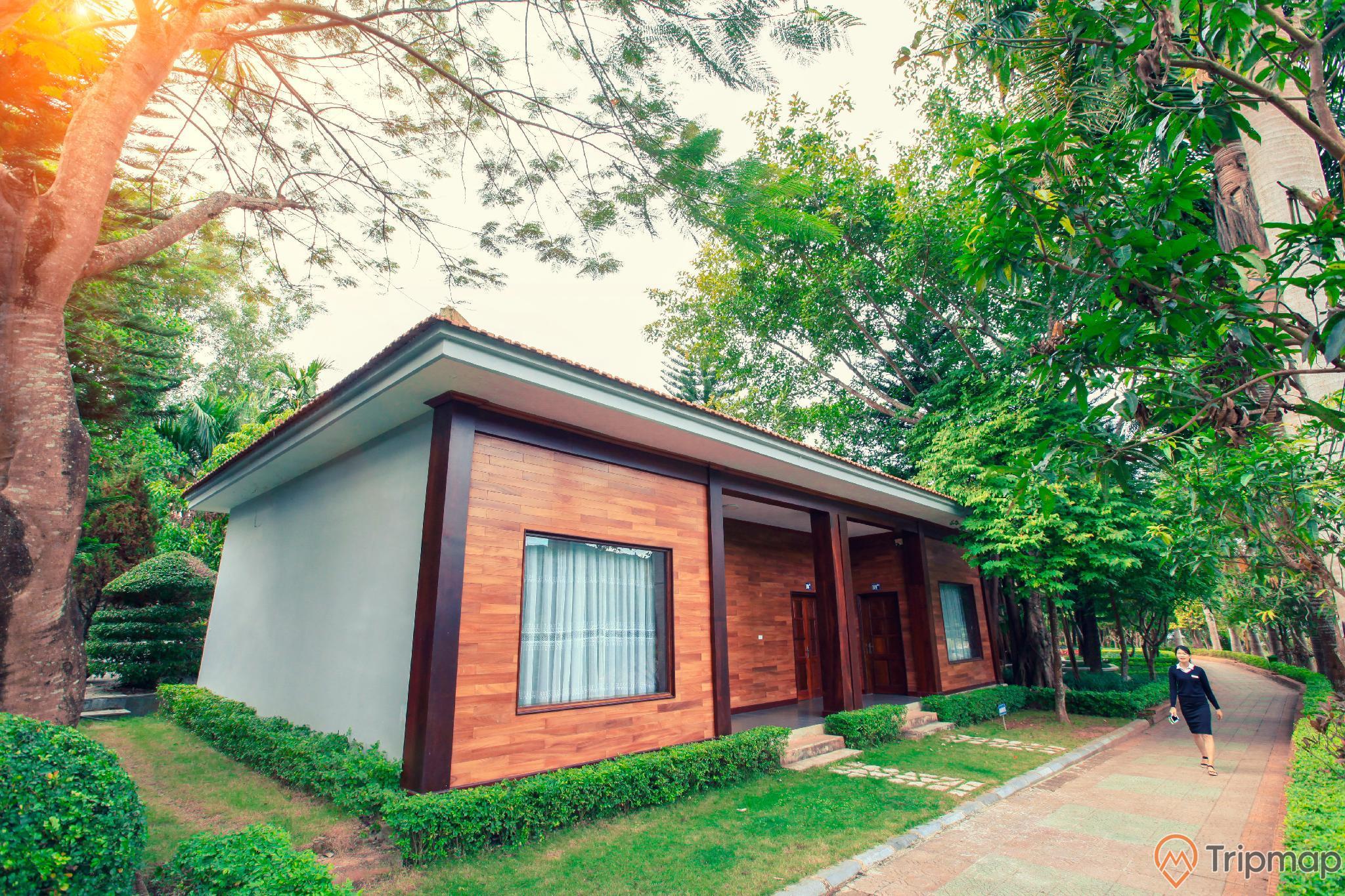Khu du lịch sinNgôi nhà trong khu du lịch sinh thái Him Lam, một người phụ nữ đang đi bộ, cây cối xanh tươi gần ngôi nhà, ảnh chụp ngoài trờih thái Him Lam