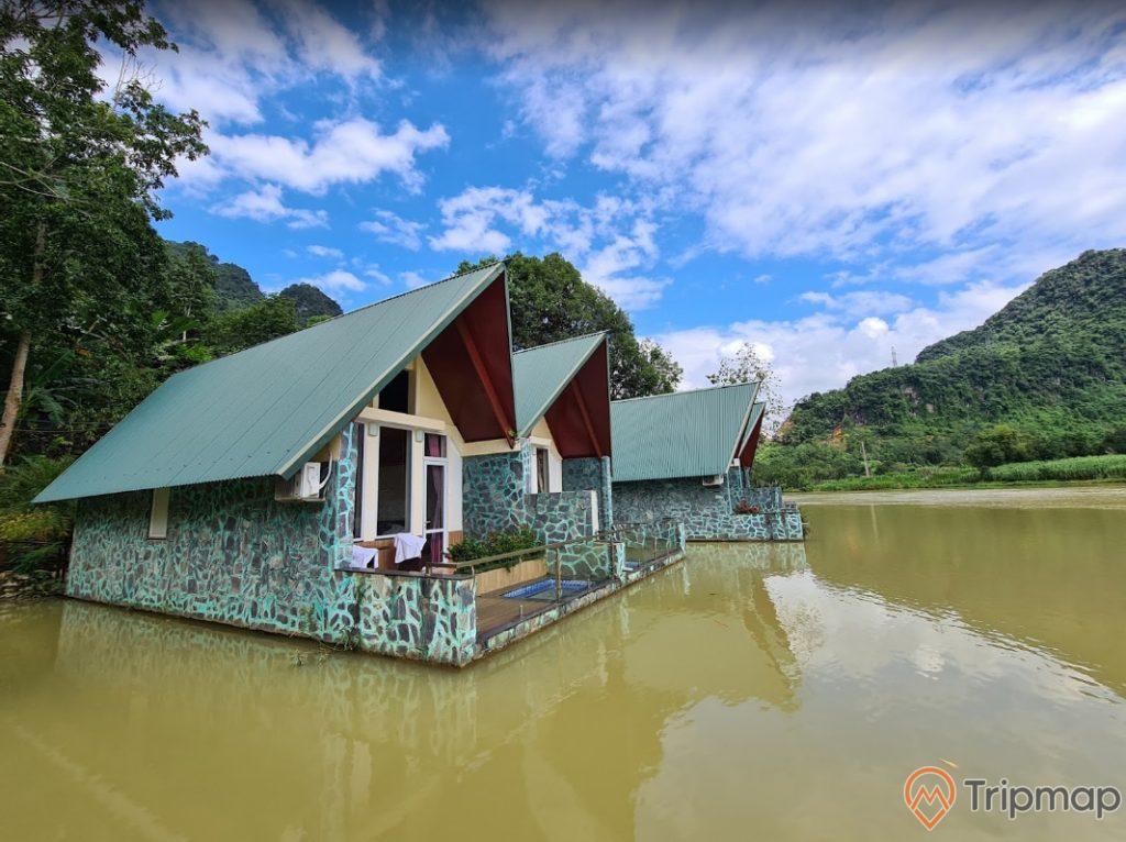 Ngôi nhà nghỉ trên dòng sông Miện tại khu du lịch sinh thái trường xuân, ngôi nhà mái tôn màu xanh lá bên dòng sông, đồi núi phía xa xa, bầu trời trong xanh nhiều mây trắng, ảnh chụp ngoài trời